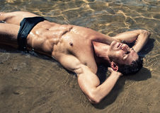 Male model in the water. Muscled male model posing in the water Stock Photos