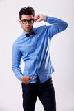 Male model wearing bow tie and holding his glasses. Young fashion male model wearing bow tie and holding his glasses on gray background Stock Photos