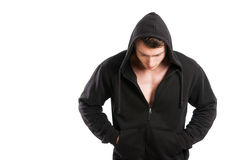Male model wearing just black hoodie and looking down Stock Photography