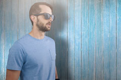 Composite image of male model wearing sunglasses. Male model wearing sunglasses against view of wooden planks Royalty Free Stock Image