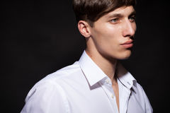 Male model in white shirt on black background Royalty Free Stock Images