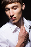 Male model in white shirt on black background Stock Photography