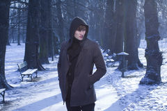Male model in winter alley, cold blue background. Male model in jacket and warm sweeter walking via blue park alley covered in snow background. Fashion concept Stock Photography