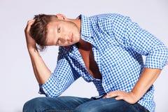 Male modell för mode som sitter mot grå bakgrund royaltyfria bilder