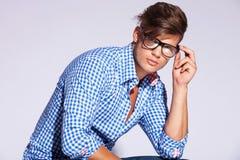 Male modell för tillfälligt mode som rymmer hans exponeringsglas royaltyfri fotografi