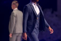 Fashion catwalk runway show models. Male models walk the runway in different suits during a Fashion Show. Fashion catwalk event showing new collection of clothes royalty free stock image