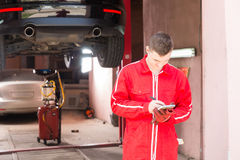 Male motor mechanic standing making notes in front of a black se. Dan elevated on a hoist in a bay in a garage or workshop Stock Images