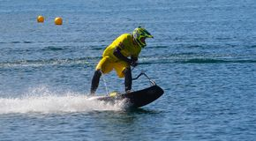 Male Motosurf Competitor moving at speed creating a lot of spray. WYBOSTON, BEDFORDSHIRE, ENGLAND - JULY 08, 2017: Male Motosurf Competitor moving at speed Royalty Free Stock Images