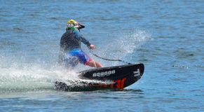 Male Motosurf Competitor Taking corner at speed creating a lot of spray. WYBOSTON, BEDFORDSHIRE, ENGLAND - JULY 08, 2017: Male Motosurf Competitor Taking corner Royalty Free Stock Image