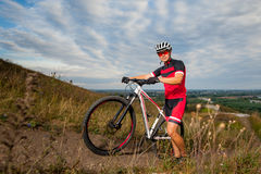 Male mountain biker resting near his bike. Male mountain biker in red sportswear resting near his bike on his way up the hill. Blue sky and over view on the city Royalty Free Stock Image
