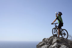 Male mountain biker sitting on bicycle at edge of rock, looking at horizon over sea, rear view Royalty Free Stock Images