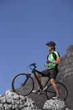 Male mountain biker sitting on bicycle at edge of rock, looking at view, side view Royalty Free Stock Photo