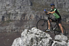 Male mountain biker sitting on bicycle at edge of rock, looking at view, side view Royalty Free Stock Images