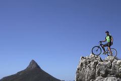 Male mountain biker sitting on bicycle at edge of rock, looking at view, side view, low angle view Stock Image