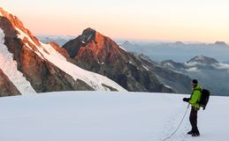 A male mountain climber stands on a high alpine glacier at dawn and admires the fantastic view ouf the surrounding landscape royalty free stock photography