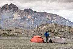 A mountain climber and two tents in a remote base camp in the Cordillera Blanca. A male mountain climber stands between two tents at a remote base camp high up stock photos