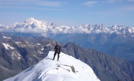 Male mountain climber on the summit of Gran Paradiso with a great view of Mont Blanc behind him. A male mountain climber on the summit of Gran Paradiso with a Stock Photos