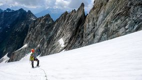 Male mountain climber takes a break on a high alpine glacier and looks at his way down and the descent route. Down to the Baltschieder Hut Royalty Free Stock Photo