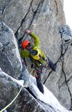 Male mountain climber traverses a tricky rock chimney on his way to a high alpine summit. A male mountain climber traverses a tricky rock chimney on his way to a Royalty Free Stock Photography