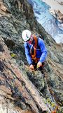 Male mountain guide building a traditional belay stance with pitons to rappel from a high alpine peak. A male mountain guide building a traditional belay stance Stock Photos