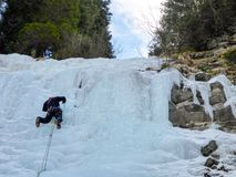 Male mountain guide lead ice climbing a frozen waterfall in deep winter in the Alps of Switzerland Stock Photo