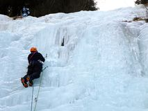 Male mountain guide lead ice climbing a frozen waterfall in deep winter in the Alps of Switzerland Royalty Free Stock Photo