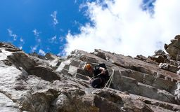 Male mountain guide rappelling off a steep rock face under a beautiful blue sky with white clouds. A male mountain guide rappelling off a steep rock face under a Stock Image