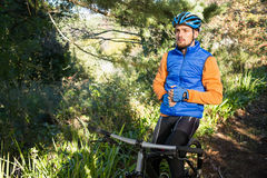 Male mountain holding water bottle standing with bicycle. In the forest Stock Images