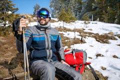 Mountaineer in snowy forest on break from mountaineering. Male mountaineer in snowy forest on break from mountaineering Stock Photos