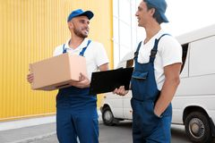 Male movers with box and clipboard stock photography