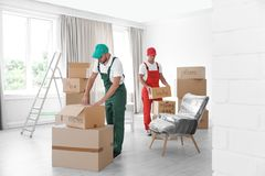 Male movers with boxes in house. Male movers with boxes in new house royalty free stock photos