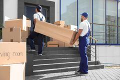 Male movers carrying shelving unit. Into new house royalty free stock photo