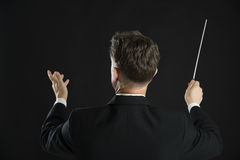 Male Music Conductor Directing With His Baton. Rear view of male music conductor directing with his baton against black background Stock Images