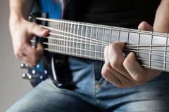 Male musician playing on bass guitar. Closeup male musician playing on bass guitar Stock Photos
