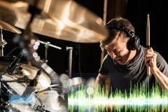 Male musician playing drum kit at concert. Music, people, musical instruments and entertainment concept - male musician in headphones with drumsticks playing Royalty Free Stock Image