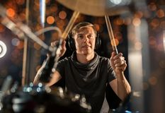 Male musician playing drum kit at concert. Music, people, musical instruments and entertainment concept - male musician in headphones with drumsticks playing Royalty Free Stock Photography