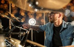 Male musician playing drums and cymbals at concert. Music, musical instruments and entertainment concept - male musician with drumsticks playing drums and Royalty Free Stock Photography