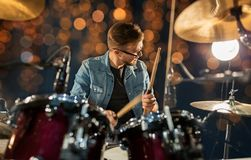 Male musician playing drums and cymbals at concert. Music, musical instruments and entertainment concept - male musician with drumsticks playing drums and Stock Photo