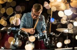 Male musician playing drums and cymbals at concert. Music, people, musical instruments and entertainment concept - male musician with drumsticks playing drums Stock Photography