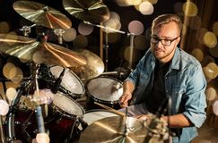 Male musician playing drums and cymbals at concert. Music, people, musical instruments and entertainment concept - male musician with drumsticks playing drums Royalty Free Stock Image