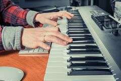 Male musician playing midi keyboard synthesizer in recording studio, focus on hands. Close-up stock photography