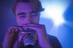 Male musician playing mouth organ in illuminated nightclub Royalty Free Stock Photos