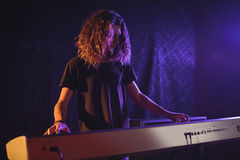 Male musician playing piano in illuminated nightclub. Confident male musician playing piano in illuminated nightclub Royalty Free Stock Images