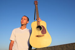 Male musician posing with an acoustic guitar outside Stock Photos