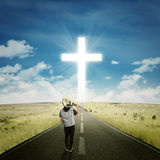 Male musician walking to the cross Royalty Free Stock Photography