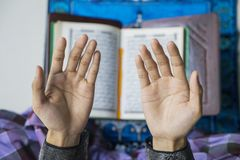Male muslim hand praying to the GOD. Closeup of male muslim hand praying to the GOD with Quran background during ramadan time stock image