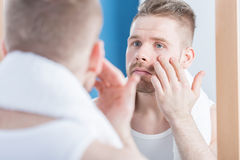 Male narcissus examining complexion Stock Photo