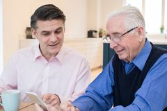Male Neighbor Showing Senior Man How To Use Mobile Phone. Male Neighbor Shows Senior Man How To Use Mobile Phone Royalty Free Stock Photo