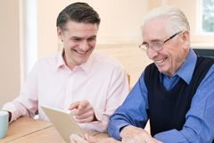 Male Neighbor Showing Senior Man How To Use Digital Tablet. Male Neighbor Shows Senior Man How To Use Digital Tablet Royalty Free Stock Photo