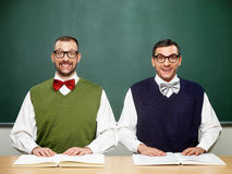 Male nerds with books. In front of the table Royalty Free Stock Photos